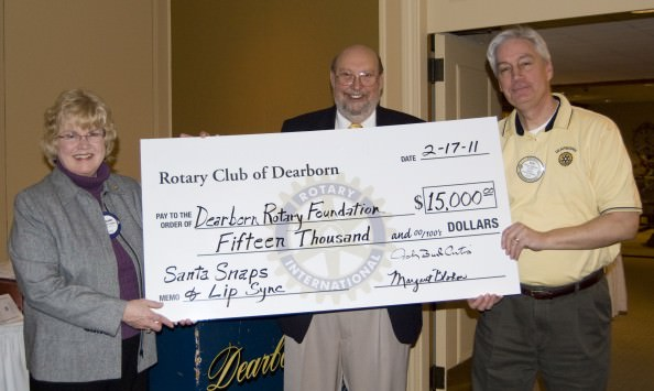 President Margaret Blohm and President-Elect John Artis present a check for 15K to Bob Gleichauf, President of the Dearborn Rotary Foundation. The money was earned at Santa Snaps and the Lip Sync program.