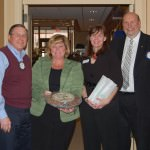 ServPro of Dearborn. Pictured from left to right are: Roger Miller, Treasurer Rotary Club of Dearborn, Maureen Winfree and Elizabeth Curran of Serve-Pro and John Artis, President Elect and Santa Snaps Chairman for the Rotary Club of Dearborn. Maureen and Elizabeth were presented with a tray of hand-made chocolates and a package of clean-up towels in gratitude for the ServPro of Dearborn donation.