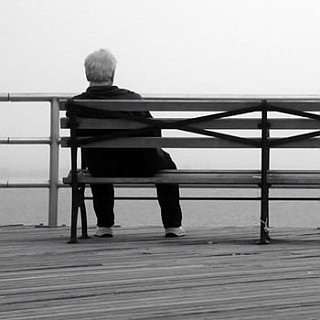 Man sits on bench - looking out at the water.