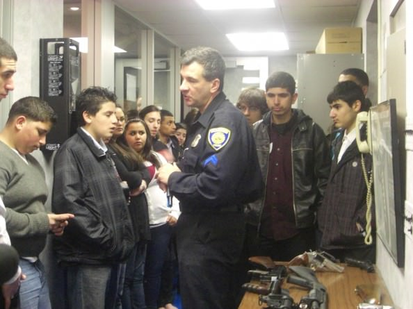 The Dearborn Youth Police Academy included demonstrations of police procedures, special units, and equipment. Here, Firearms Coordinator Steve White shows the students some of the department's inventory. The successful academy was designed to strengthen relationships between the students and officers.