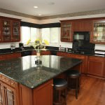 Gourmet kitchen includes lovely cherry cabinets, dramatic charcoal granite counters, a hardwood floor, planning desk, large granite island, and table space.