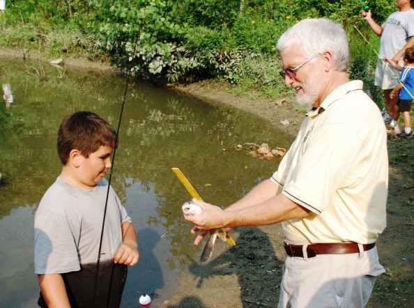 Rotarian Rick Enright measures a fish for one of the lucky fishermen.
