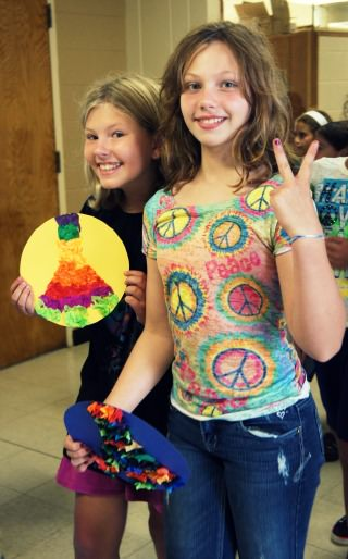Sixth grade students Aliyah Moline-Freeman, at left, and Abby Mills carry symbols of peace during the Peace Day celebration at Dearborn Heights Montessori Center.