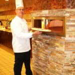 Executive Chef Pearse Tormey readies a pizza for Oakwood Common's pizza oven in the community's bistro café.