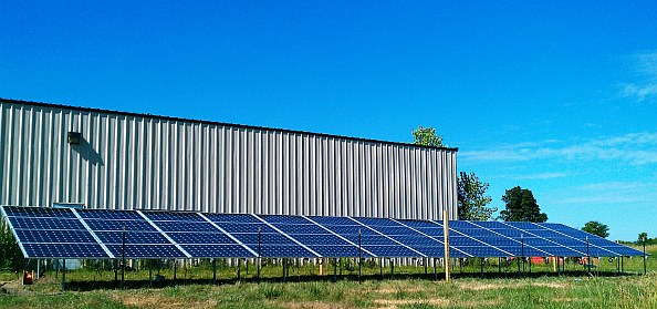 Ground-mounted solar panels provide energy savings to the main Amma Center building.