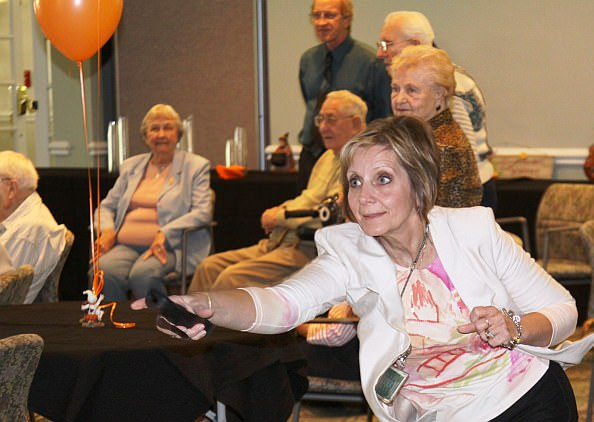 Oakwood Common staffer Judy Antinossi gives an enthusiastic toss as residents and staff watch.