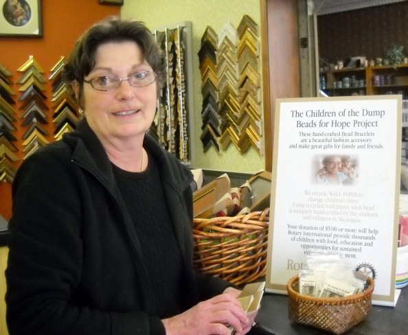 """Mary Ray of Campbell's Paint & Wallpaper stands next to the """"Beads of Hope"""" display in her Dearborn store."""