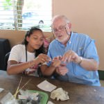 "Dearborn Rotarian Ray Trudeau receives a lesson about making ""Beads of Hope"" from recycled wallpaper during a recent trip to Nicaragua."