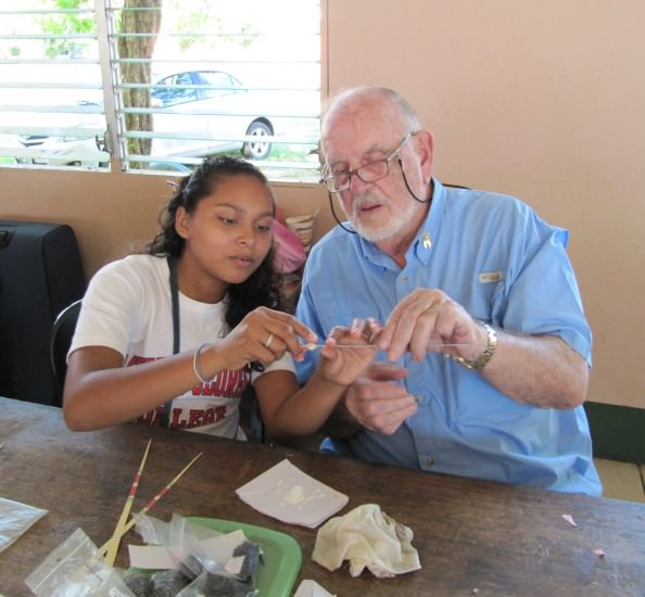 """Dearborn Rotarian Ray Trudeau receives a lesson about making """"Beads of Hope"""" from recycled wallpaper during a recent trip to Nicaragua."""