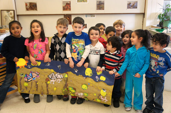 A group of DHMC preschoolers proudly display their African desert mural.  In front, left to right, are Zharia Hunter, Fatima Farhat, Danny Hassan, Joshua Liparoto, Attilio Rugiero, Rayan Jomaa, Diala Sobh and Ali Khierbek, and back row, l. to r., Rami Ela Ali, Yaseen Khalil, Faudel Nazal and Christina Fehme.