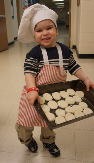 Henry Maliszewski, age 3, dons his baking gear in the Toddler program at Dearborn Heights Montessori Center.
