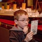 Young boy examines boarding pass for the RMS Titanic at Titanic Exhibit.