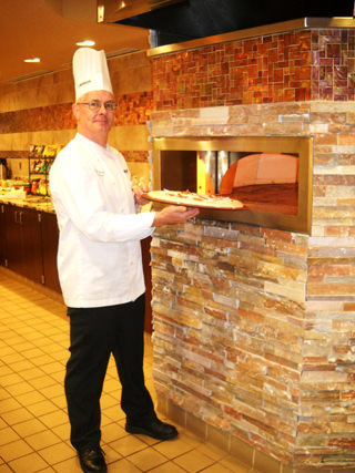Chef Pearse Tormley of Oakwood Common prepares pizzas for Oakwood Common residents and guests.