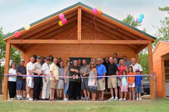Camp Dearborn marked the opening of eight new resort cabins at the recreational facility on June 16, adding a more modern option for vacationing at the family-friendly campground.  Shown here (with scissors) are Dearborn Mayor John B. O'Reilly, Jr., and Milford Township Supervisor Donald Green. Among the celebrants were Dearborn City Council members Robert Abraham and Mark Shooshanian. Dearborn Recreation Commissioners Jeff Stassen, John Sczomak and John Ruselowski were joined by Joanne Murphy of the Friends of Camp and Recreation and Parks Director Greg Orner, as well as staff members Teddy Shaskos, Eric Peterson, Lee Morris, Peggy Schous and Al and Linda Dyer. City of Dearborn department directors also showed support for the new cabins.