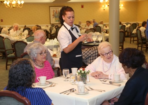 Server Maricruz Garcia prepares table service in Oakwood Common's Acorn Dining Room as Mattie Edwards, from left, Irene Brown, Margaret Schultz and Louise Eason visit before dinner is served.