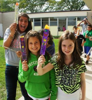 Fifth grade students, from left, Jenna Dabaja, Grace Audi and Mila Nowlan, carry symbols of peace around the school during the International Peace Day celebration at Dearborn Heights Montessori Center.
