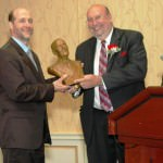 New 2012-2013 Dearborn Rotary President, Hassen Hammoud, at left, receives bust of Rotary Founder, Paul Harris, from 2011-2012 Dearborn Rotary Past President, John Artis at the annual President's Dinner.