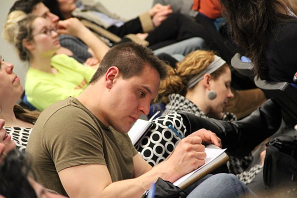 Students taking listening and taking notes at InterVarsity sponsored lecture on Thursday evening, April 18.