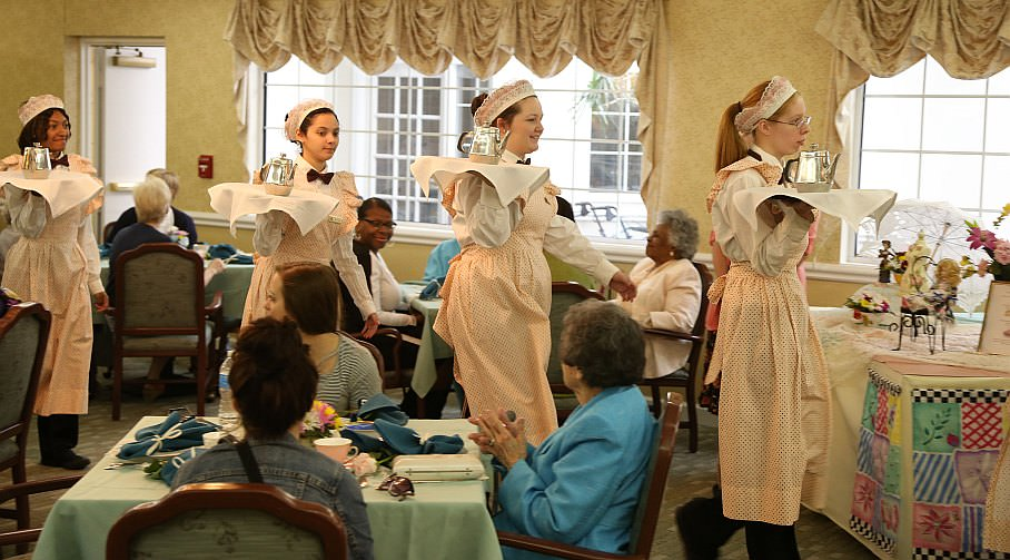 Wait staff dressed in Victorian period costumes prepare to serve residents and guests at Oakwood Common's annual Mother's Day Tea.