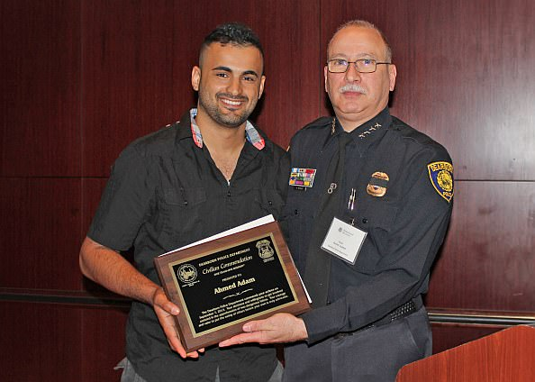 Dearborn resident Ahmed Adam with Chief of Police Ronald Haddad. Adam was  recognized for his efforts in helping to prevent a crime in Dearborn.