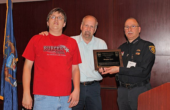 Dearborn resident Douglas Berry and his son, Patrick, with Chief of Police Chief Ronald Haddad. Berry was recognized for his efforts in helping to prevent a crime in Dearborn.