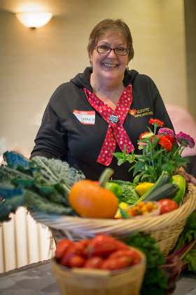 Volunteer auctioneer with fun food baskets from 2012 event.