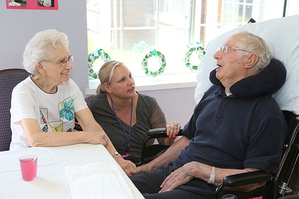 Activities Director Angie Gielow visits with Elaine Gasser and her husband Eugene Gasser, a long-term resident of the skilled nursing area, during the noon hour.