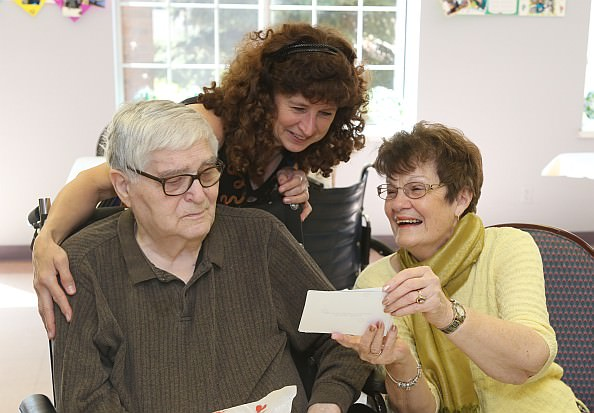 Carl Borsodi, a resident of Oakwood Rehabilitation and Skilled Nursing, looks at photos with his wife Shirley Borsodi, and daughter Theresa Borsodi, who was visiting from Boston.