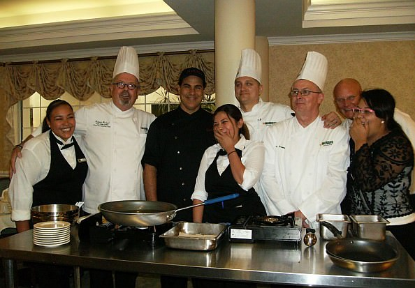 Chef Santaella, center, and the Morrison chefs and staff, share a playful moment before doors opened for the residents.