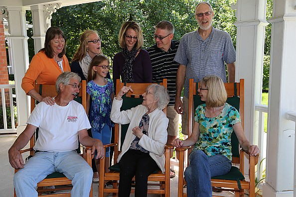 Sue Wright, center front, sparkles during a family gathering on the porch of Sunrise of Northville. Pictured from l. to r., back row, are Debby, Savannah, Ella, Karen and Zack Wright with brother-in-law Doug Clare; in rocking chairs by Sue are Doug Wright and Marta Clare.