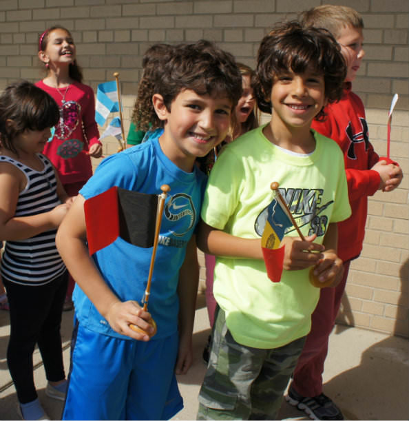 First graders Yousef Mehanna, at left, and Yousef Darwich, carry flags during DHMC's Peace Day celebration.