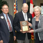 John Fish, Jr., center, shares Dearborn Rotarian of the Year plaque with his wife Mary. At left, Dearborn Rotary's treasurer and 2012-2013 winner Roger Miller made the presentation.