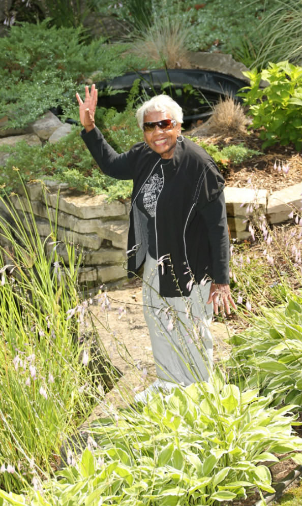 Oakwood Common resident Ramona Redd waves to others from the garden below her apartment.
