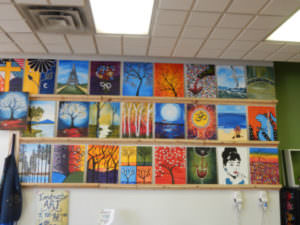 Wall next to stage displaying instructor's art for sale.